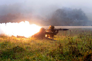Soldiers fire a rocket propelled grenade at opposing forces.の写真素材 [FYI02851480]