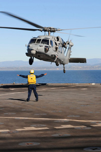 Boatswain's Mate directs an MH-60S Sea Hawk helicopter on the flの写真素材 [FYI02851550]