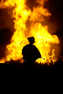 U.S. Army Sergeant monitors the flames of a fire around a caの写真素材 [FYI02851636]