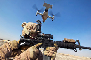 A soldier provides security as an MV-22 Osprey lands in Afghanistan.の写真素材 [FYI02851734]
