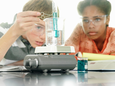 Teenage boy and girl (15-17) doing science experiment at desk in classroom, surface levelの写真素材 [FYI02852126]