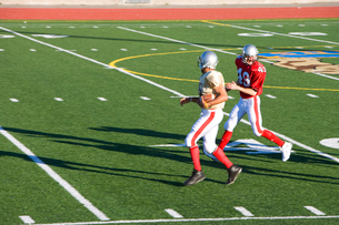 American football player chasing opposing receiver with ball during competitive game, side viewの写真素材 [FYI02852233]