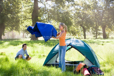 Young man crouching near dome tent on camping trip in woodland clearing, woman holding blue sleepingの写真素材 [FYI02852295]
