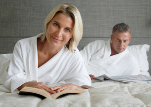 Couple in bathrobes relaxing on hotel bed, man reading newspaper, focus on woman with bookの写真素材 [FYI02852300]