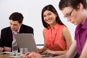 Three business people sitting at conference table, focus on businesswoman using laptop, smiling, porの写真素材 [FYI02852319]