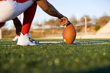 American football player attempting to kick field goal, teammate holding ball vertically against pitの写真素材 [FYI02852329]