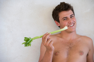 Bare chested young man with celery stick, smiling, portraitの写真素材 [FYI02852344]