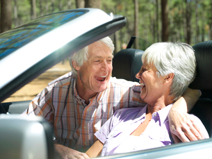 Senior couple sitting in convertible car, laughing, side viewの写真素材 [FYI02852345]