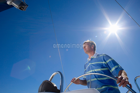 Man in striped blue polo shirt standing at helm of sailing boat out at sea, steering, low angle viewの写真素材 [FYI02852347]