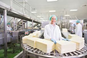 Portrait smiling worker with large blocks of cheese at production line in processing plantの写真素材 [FYI02852348]