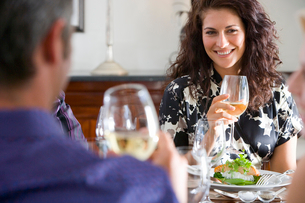 Couple holding glasses of wine at lunch table, smiling at each otherの写真素材 [FYI02852351]