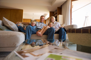 Two generation family relaxing on sofa at home, smiling, front view, portraitの写真素材 [FYI02852362]