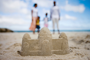 Two generation family standing on beach, focus on sandcastle in foreground, surface levelの写真素材 [FYI02852390]