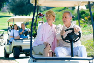 Two mature couples driving golf buggies along golf course pathway, focus on couple in foreground, smの写真素材 [FYI02852391]