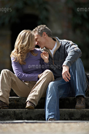 Affectionate couple sitting on steps, man whispering in woman's ear, smilingの写真素材 [FYI02852394]