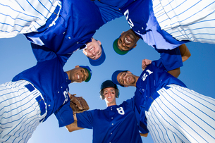 Baseball team, in blue uniform, standing in huddle, smiling, portrait, upward viewの写真素材 [FYI02852406]
