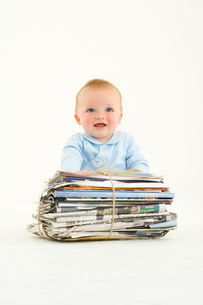 Baby boy (3-6 months) by bundle of newspapers, smilingの写真素材 [FYI02852414]