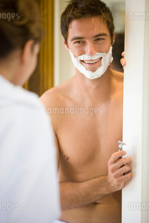 Man preparing to shave, smiling at woman (differential focus)の写真素材 [FYI02852421]