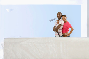 Smiling couple with paint roller standing next to freshly painted living room wallの写真素材 [FYI02852424]