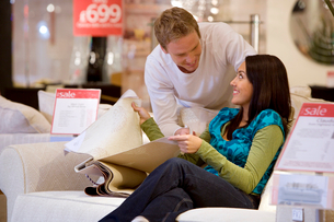 Young couple with fabic samples in shop, smiling at each otherの写真素材 [FYI02852442]