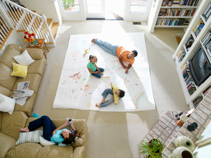Family of four in living room, drawing on large piece of paper on floor, elevated viewのイラスト素材 [FYI02852457]