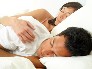 Young couple asleep in bed, woman embracing man, close-upの写真素材 [FYI02852467]