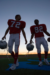 Two American football players leaving pitch at sunset, side by side, front view (surface level, backの写真素材 [FYI02852468]