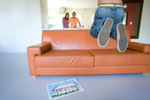 Boy(6-8) jumping by sofa, couple embracing in background, smiling, portraitの写真素材 [FYI02852473]