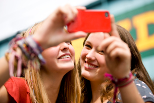 Two teenage girls taking a photograph of themselves in Camdeの写真素材 [FYI02852505]