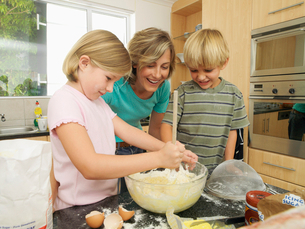 Mother and children (5-8) making cake mix in kitchen, smiling, girl stirring with wooden spoonの写真素材 [FYI02852508]