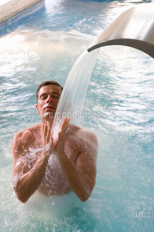 Man with eyes closed standing under swimming pool fountainの写真素材 [FYI02852511]