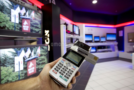 Man with credit card machine in shop, close-upの写真素材 [FYI02852512]