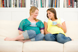 Two young pregnant women on sofa with mugs resting on stomachs, smiling at each other, low angle vieの写真素材 [FYI02852513]