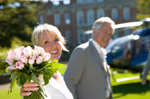 Bride with father by helicopter, smiling, focus on bouquetの写真素材 [FYI02852515]