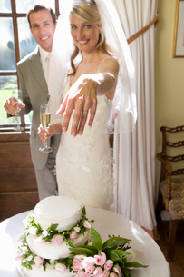 Bride and groom by wedding cake, bride showing off ring, smiling, portrait (focus on hand)の写真素材 [FYI02852548]