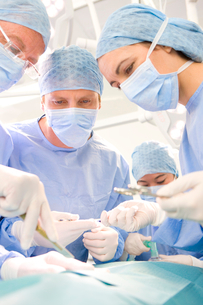 Surgeons performing operation in hospital operating roomの写真素材 [FYI02852560]