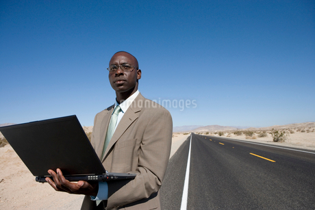 Businessman with laptop computer on road in desert, low angle viewの写真素材 [FYI02852574]