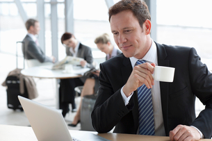 Smiling businessman drinking coffee and using laptopの写真素材 [FYI02852577]