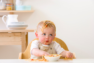 Messy baby boy in high chair eating spaghettiの写真素材 [FYI02852585]
