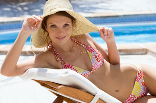 Woman in sun hat laying on lounge chair at poolsideの写真素材 [FYI02852600]
