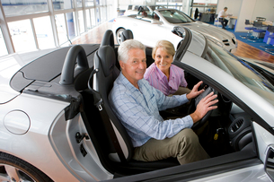 Couple looking at new cars in showroomの写真素材 [FYI02852611]