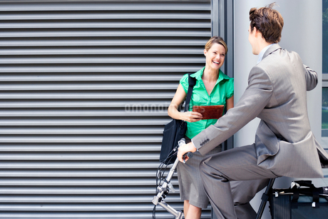 Businessman cycling on folding commuter bicycle flirting with businesswoman standing on pavementの写真素材 [FYI02852642]