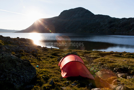 Tent at lakeshore against mountainsの写真素材 [FYI02852706]