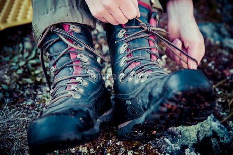 Low section of female hiker tying laces of hiking bootsの写真素材 [FYI02852751]