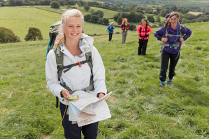 Portrait of smiling girl with backpack compass and map in fieldの写真素材 [FYI02852757]
