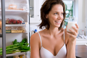 Young woman in underwear with drink by open door of fridge, smilingの写真素材 [FYI02852759]