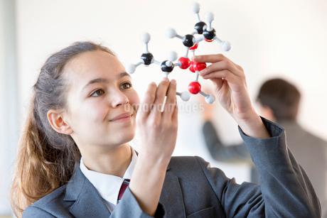 Smiling high school student examining molecule model in science classの写真素材 [FYI02852760]
