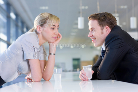 Happy businessman and businesswoman drinking water and talking face to face in officeの写真素材 [FYI02852763]
