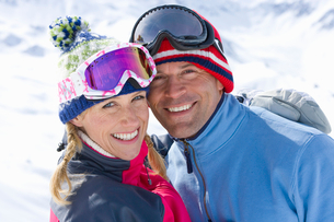 Smiling couple wearing goggles, huggingの写真素材 [FYI02852770]