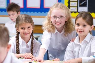 School girls smiling in classroomの写真素材 [FYI02852780]
